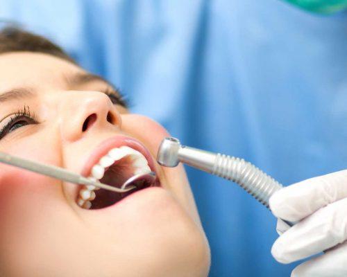periodontist examining woman's teeth